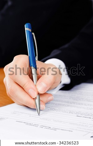 Pen in man's hand, filling the tax form