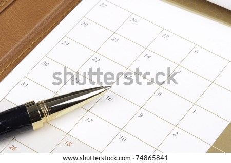Pen laying on a calendar reading to make entries into the dates for appointments and future commitments