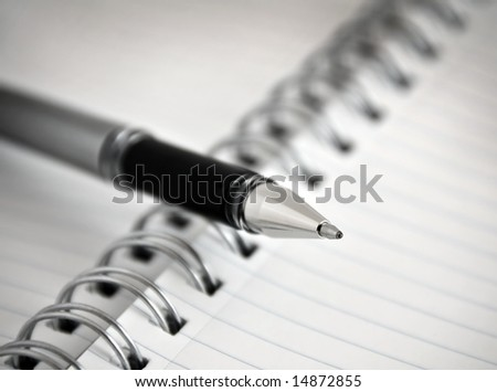 Pen laying on spiral notebook or notepad with lined paper.