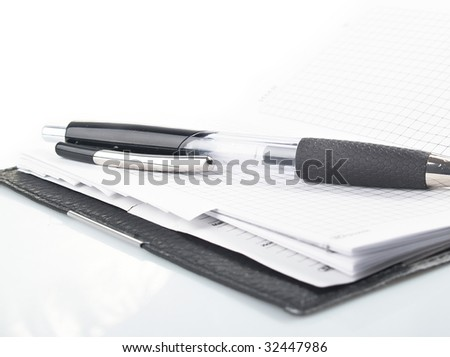 pen lying on opened notebook on isolated