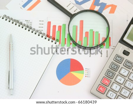 Pen, magnifying glass and calculator on paper table with diagram