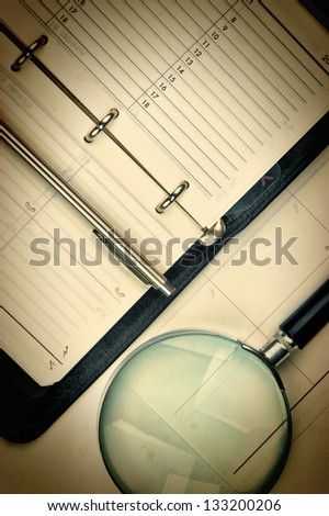 pen, magnifying glass and the diary