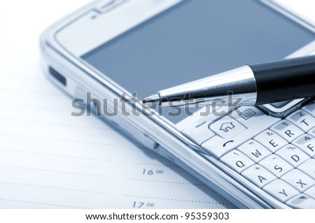 Pen, mobile phone and planner - stock photo