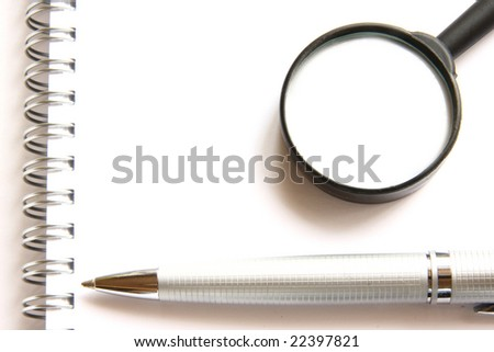Pen, notebook and magnifier