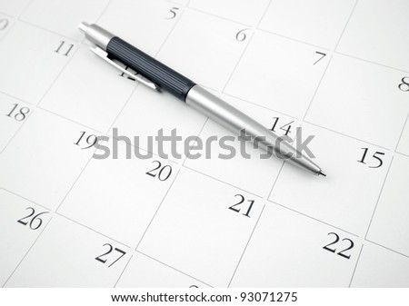 Pen on a calendar page - stock photo