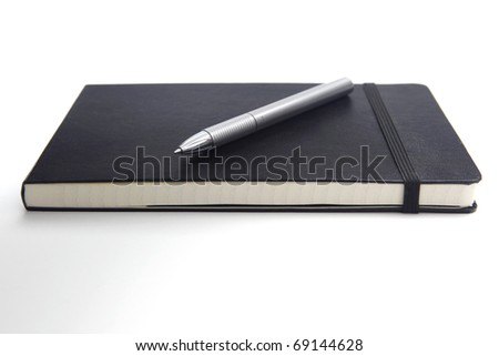Pen on a closed notebook, isolated on white background