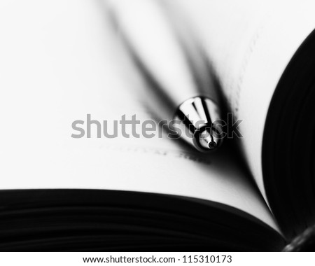 Pen on a opened book. Macro image.