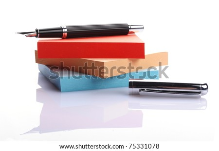 pen on a stack of colored notes on white background