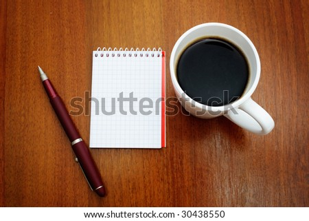 Pen on a white spiral squared notebook with cup of coffee viewed from above