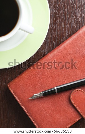 pen on diary and coffee mug
