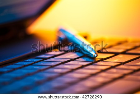 pen on laptop keyboard with shallow depth of field