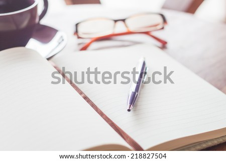 Pen on notebook with coffee cup and eyeglasses, stock photo
