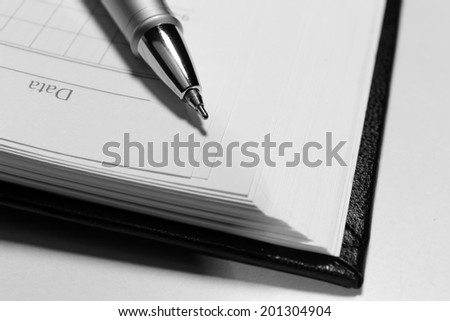 Pen on opened book, close up