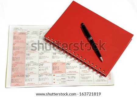 Pen over notebook on Christmas calendar isolated on white background.