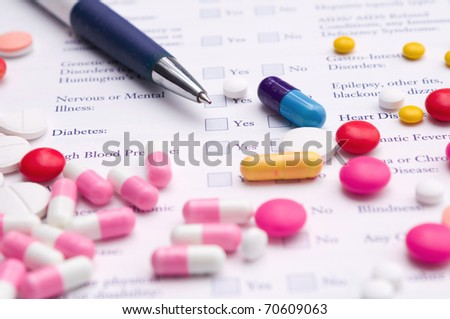 Pen, pills variety and medical certificate form that requires to fill out his required information. Focus on blue capsule