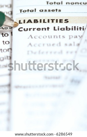 Pen pointing on liabilities section in the balance sheet