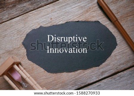 Pen, sand clock, and piece of black paper written with Disruptive Innovation on wooden background.