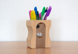 Pen tray in the form of a pencil sharpner, on a wooden desk