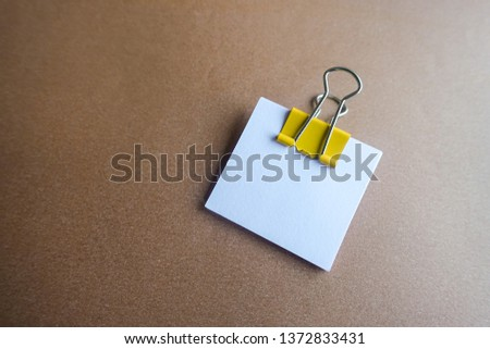 Pen, yellow paper clip and blank paper on a brown background #1372833431