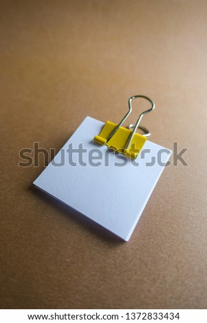 Pen, yellow paper clip and blank paper on a brown background #1372833434
