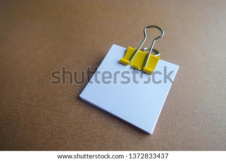 Pen, yellow paper clip and blank paper on a brown background #1372833437