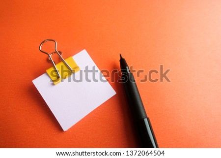 Pen, yellow paper clip and blank paper on a orange background #1372064504