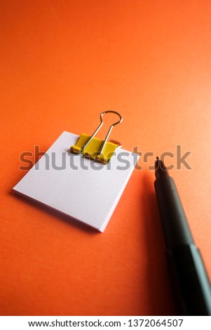Pen, yellow paper clip and blank paper on a orange background #1372064507