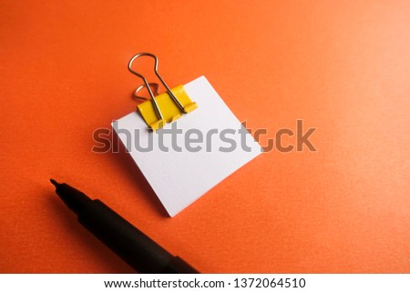 Pen, yellow paper clip and blank paper on a orange background #1372064510