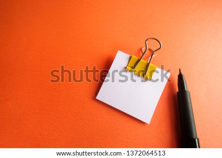 Pen, yellow paper clip and blank paper on a orange background #1372064513