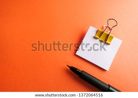 Pen, yellow paper clip and blank paper on a orange background #1372064516