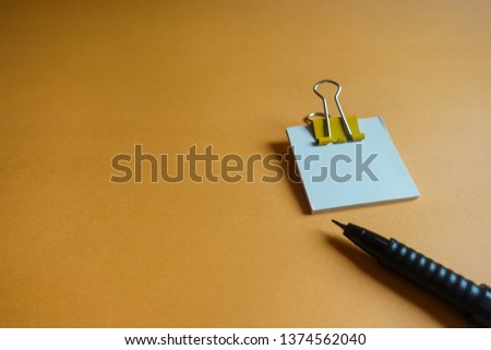 Pen, yellow paper clip and blank paper on a orange background #1374562040