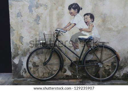 PENANG, MALAYSIA-FEB 14: Street Mural tittle 'Little Children on a Bicycle' painted by Ernest Zacharevic in Penang on Feb.14, 2012.  It was painted in conjunction with the 2012 George Town Festival.
