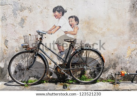 PENANG, MALAYSIA-NOV 24: General view of a mural 'Little children on a bicycle' painted by Ernest Zacharevic in Penang on Nov 24, 2012. The mural is one of the 9 murals paintings in early 2012. - stock photo