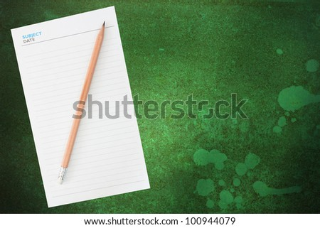Pencil and blank notepad on grunge background