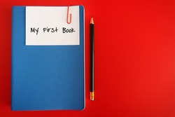 Pencil and blue notebook with note written MY FIRST BOOK , concept of goal setting for writing book project, finish it and publish it