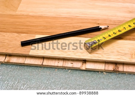 Pencil and measure tape on the wooden parquet floor