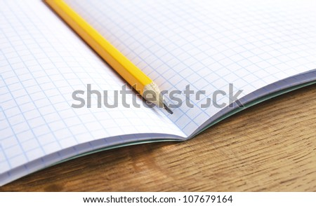 pencil and notebook on wood