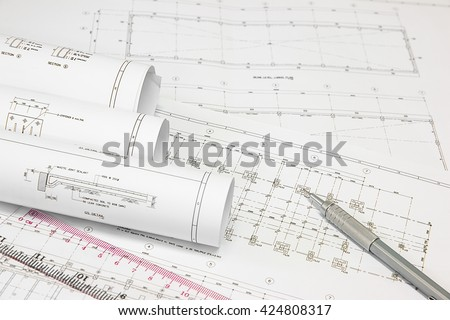 pencil and office tools for writing on the blueprint of construction industry. Place the rolls on a desk over blurred blueprint for construction industry background. construction industry concept.