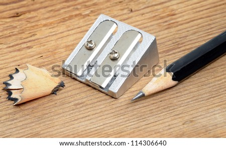 Pencil and pencil sharpener in front of a white background