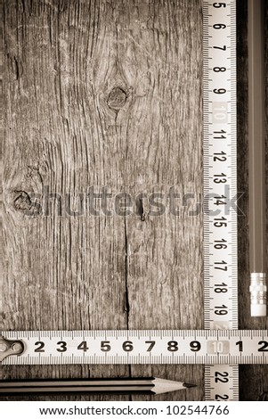 pencil and tape measure on wood texture