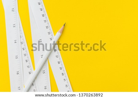 Pencil and white measuring tapes with centimetre and inches on vivid yellow background, length, long or maker instrument and tools concept.