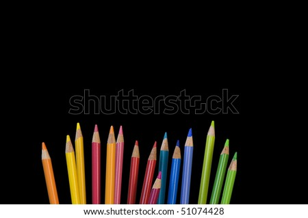 pencil crayons on black background - room for text - stock photo