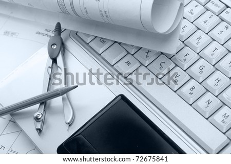 Pencil, dividers and blueprint on a laptop