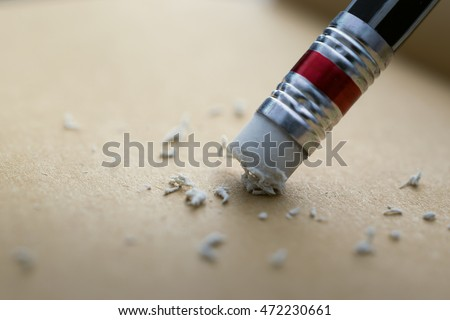pencil eraser. pencil eraser removing a written mistake on a piece of paper.