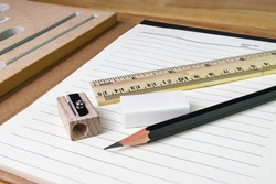pencil, eraser,ruler with book on woodtable