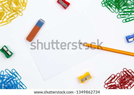 Pencil, eraser, sharpener, paper clips lie in different angles of the sheet on a white background. Hero image and copy space
