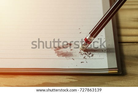 pencil eraser with eraser dust on notebook, remove pencil drawing from notebook in close up view, mistake and error concept #727863139