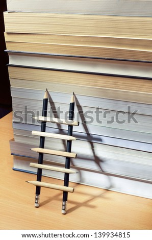 Pencil ladder leaning against a pile of books
