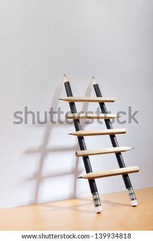 Pencil ladder leaning against white wall with copy space