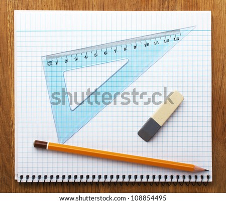 pencil notebook and eraser on wooden desk